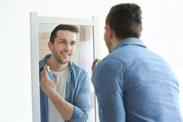 man spraying cologne in the mirror