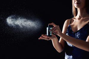 women spraying perfume